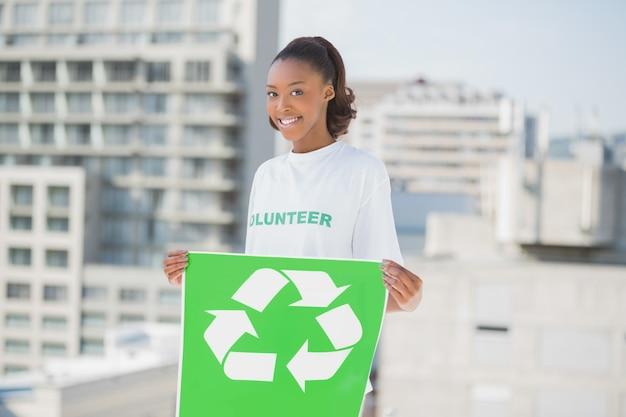 リサイクルサインを持っている幸せな利他主義女性