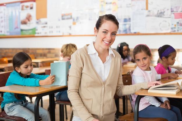 Довольно учитель улыбается на камеру с ее класс