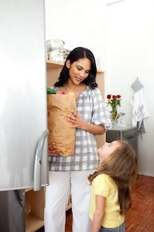Веселая девочка распаковывает продуктовый портфель с матерью