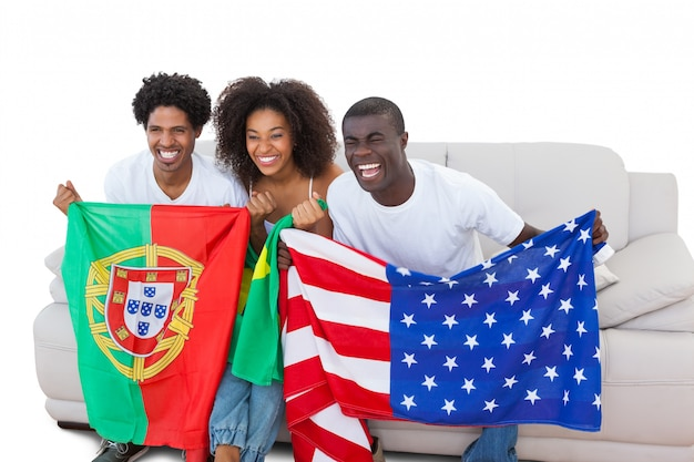 ソファに旗を抱いているサッカーファンを応援する