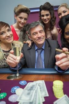 ルーレットテーブルで男性を囲む女性