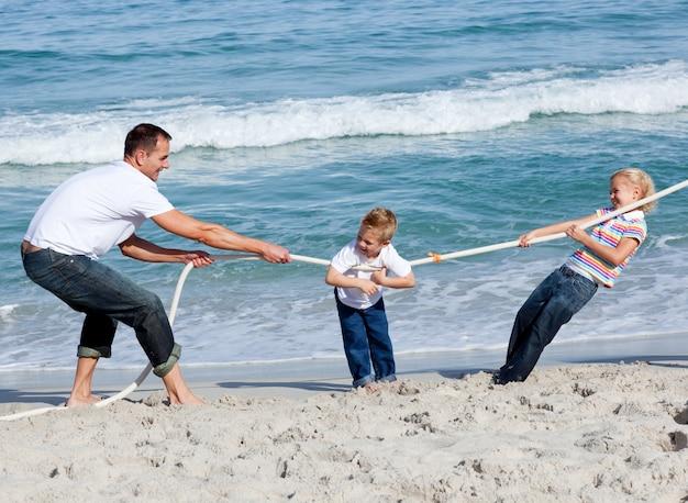 Счастливая семья играет перетягивание каната