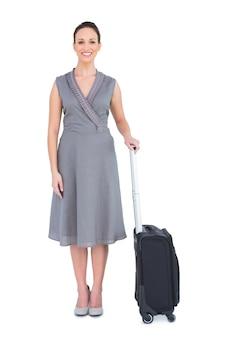 彼女のスーツケースのポーズをとった陽気で豪華な女性