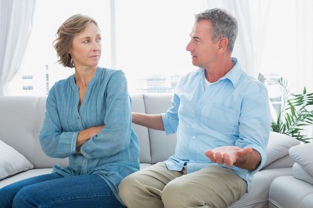 紛争のあるソファに座っている中年のカップル
