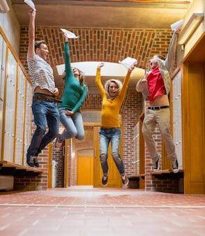 大学の廊下でジャンプする学生のグループ