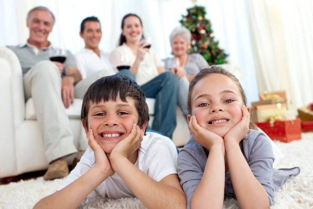 クリスマスに家族と一緒に弟と妹が床に座っています
