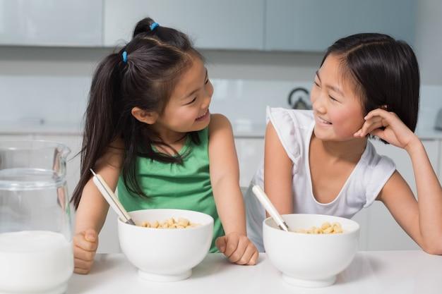 二つの笑顔の若い女の子が穀物の台所に座ってキッチンで