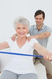 Мужской терапевт, помогая старшей женщине с упражнениями