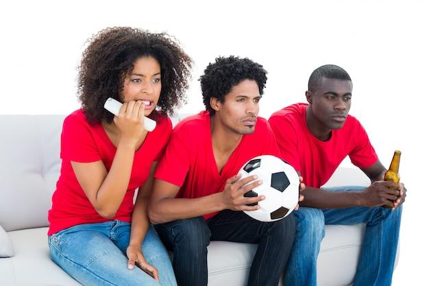 ソファに座っている赤の神経質なサッカーファン