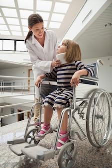 医者、車椅子で首輪をした子供と話す