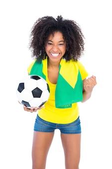 カメラで応援しているブラジルの国旗を保持しているかなりのサッカーファン