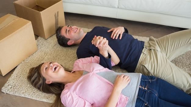 ボックスを動かして床に横たわっている笑うカップル