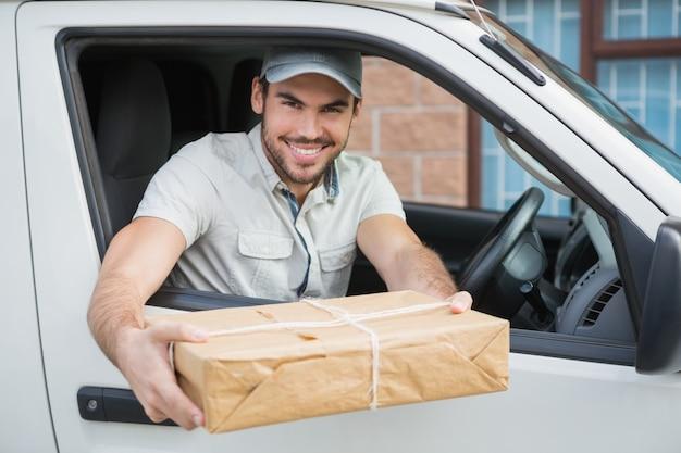 Продавец доставки, предлагающий посылку из своего фургона