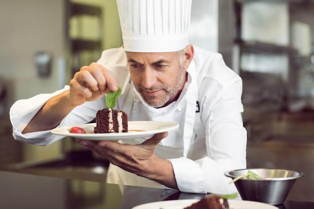 Концентрированный мужской шеф-повар, украшающий десерт на кухне