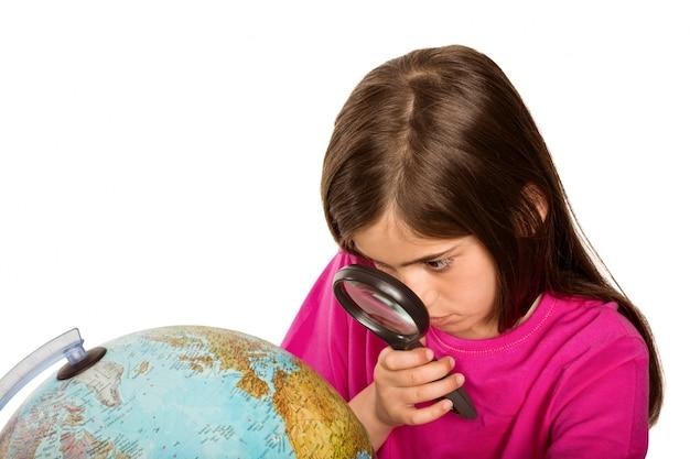 かわいい瞳孔は、虫眼鏡を通して地球儀を見て
