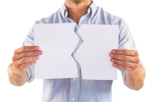 裂かれた白い紙を持っている男