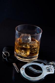 Виски на скалах с ключом автомобиля и наручниками