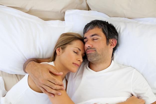 思いやりのある恋人たちがベッドに横たわっている