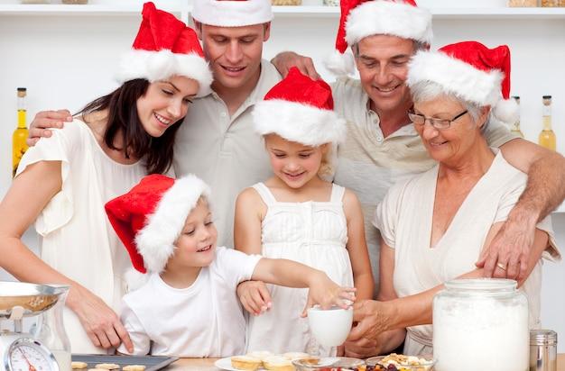 キッチンでクリスマスケーキやお菓子を焼く家族