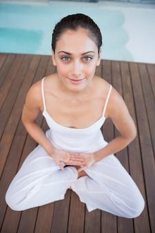 白い蓮のポーズで座って平和なブルネット
