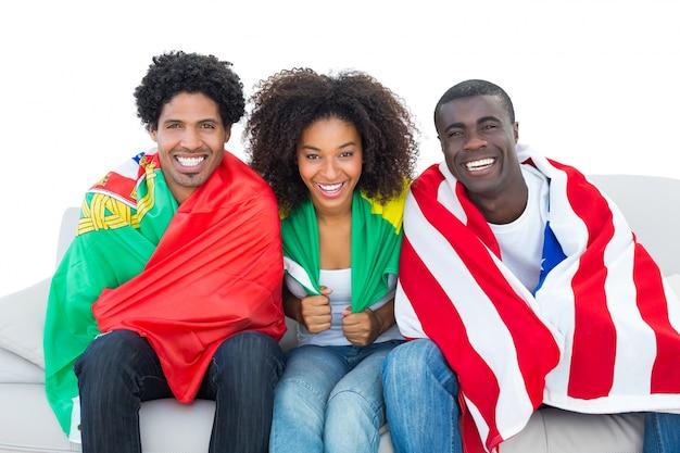 カメラで笑う旗に包まれた幸せなサッカーファン