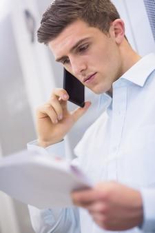 若い技術者が電話をかけて文書を読む