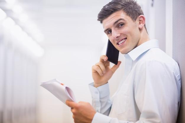 ドキュメントを持っている電話で笑顔の技術者