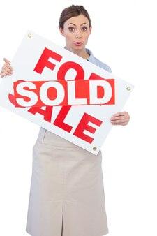 それの向こうに販売されたステッカーで販売サインを示す不動産業者