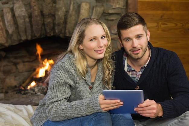 Пара, используя планшетный пк перед освещенным камином