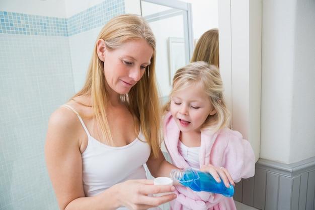 娘と青いうがい薬を注ぐ幸せな女性