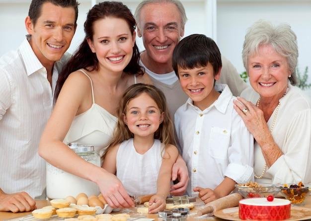 両親、祖父母、キッチンで焼く子どもたちの肖像