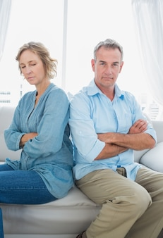紛争後に話していないソファに座っている中年のカップル