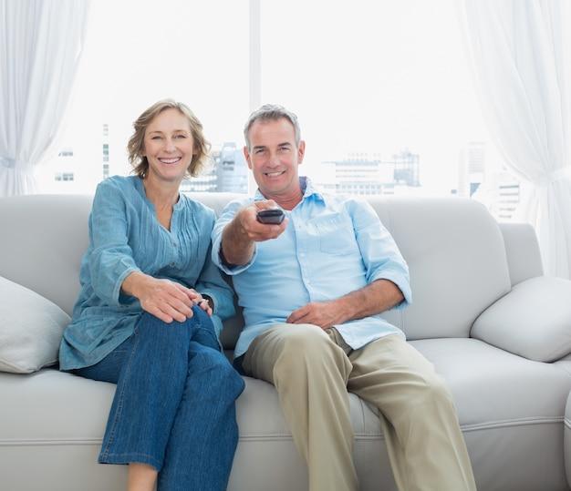 テレビを見てソファに座ってコンテンツの中年カップル