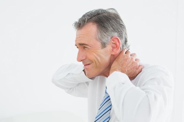 首の痛みに苦しんでいる成熟した男の側面図