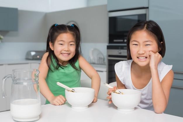二人の笑顔の女の子の肖像画は、台所に座って