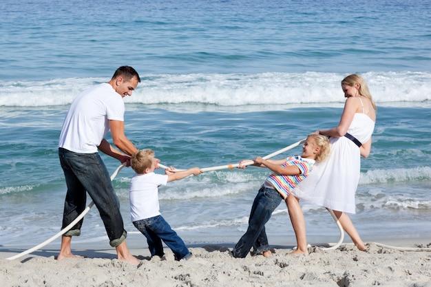 Возбужденная семья, играющая в перетягивание каната