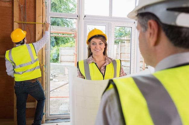 男が測定中に建築家に笑みを浮かべている女性