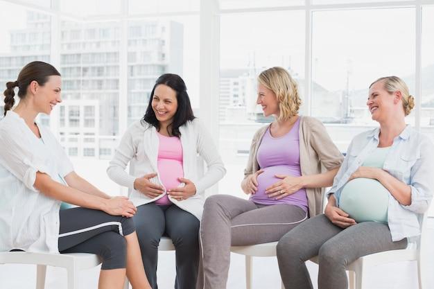 出産前のクラスで一緒に話している幸せな妊婦