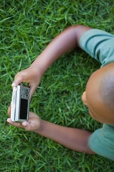 デジタルカメラを見ながら芝生に横たわる小さな男の子