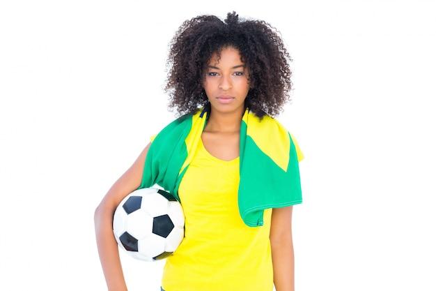 カメラを見ているブラジルの国旗を保持しているかなりのサッカーファン