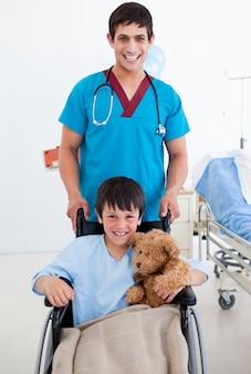 車椅子と医者に座っているかわいい少年の肖像