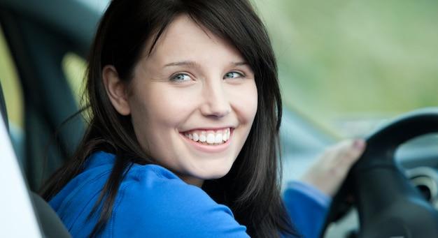 Яркая женщина-водитель сидит в машине