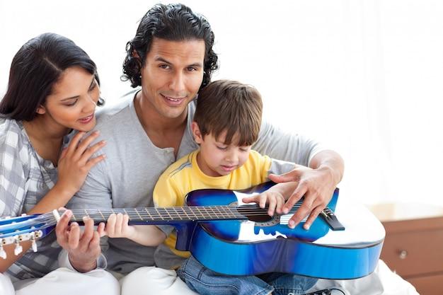 両親と一緒にギターを弾いているかわいい少年