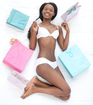 ベッドに横たわっているクレジットカードを持っている幸せな女性