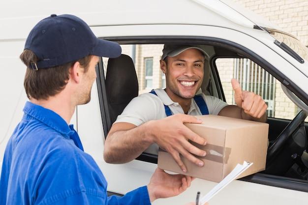 彼のバンの顧客に小包を渡す配達ドライバー