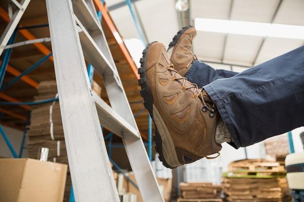 Работник падает с лестницы на складе
