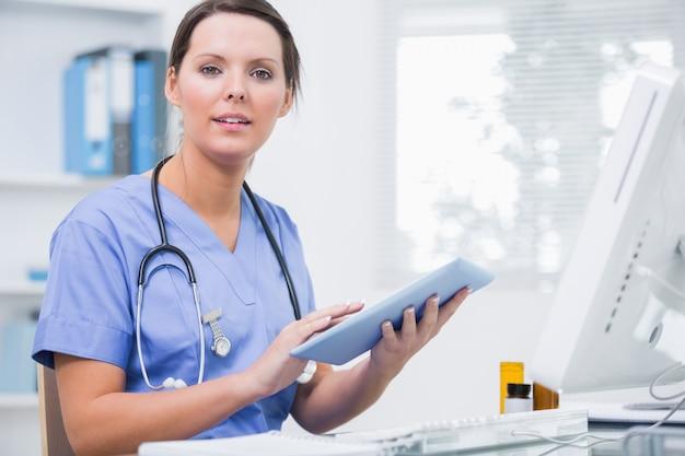 Портрет хирурга с использованием цифрового планшета перед компьютером в клинике