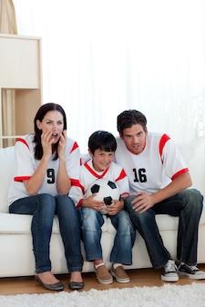 集中している家族見ているサッカーの試合