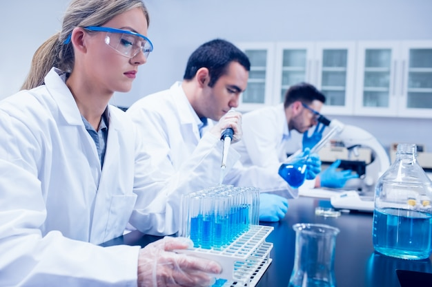 Учащийся-наука, используя пипетку в лаборатории, чтобы заполнить пробирки