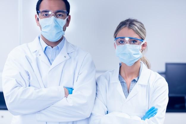 Научные ученики, надевающие защитные маски